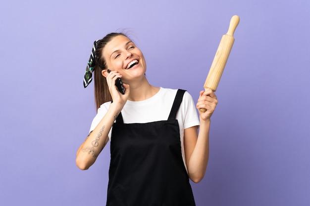 Femme slovaque cuisinière isolée sur mur violet en gardant une conversation avec le téléphone mobile