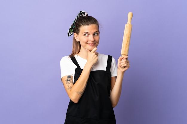 Femme slovaque cuisinière isolée sur mur violet en pensant à une idée tout en regardant