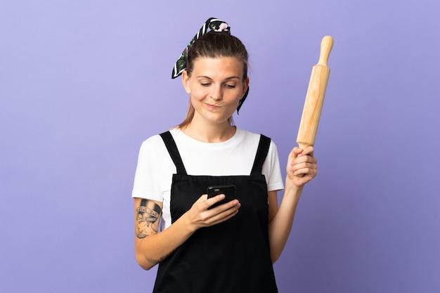 Femme slovaque cuisinière isolée sur mur violet penser et envoyer un message