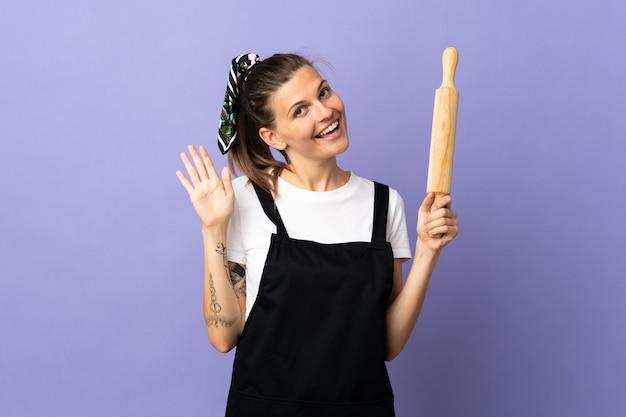 Femme slovaque cuisinière isolée sur mur violet saluant avec la main avec une expression heureuse