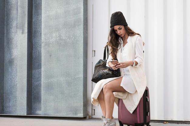 Femme avec smartphone assis sur la valise