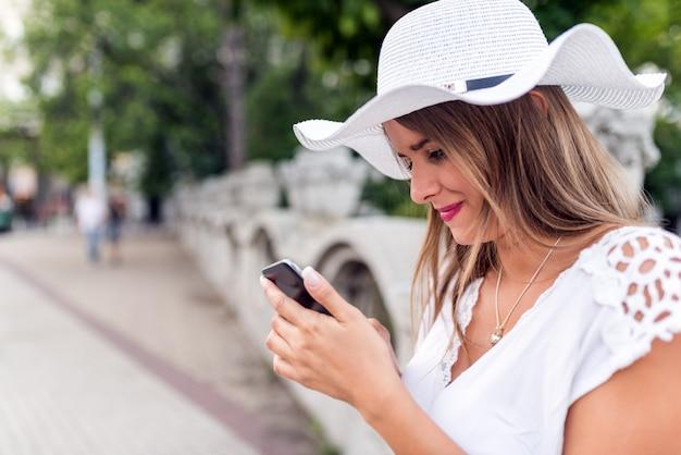 Femme avec le smartphone à l'extérieur