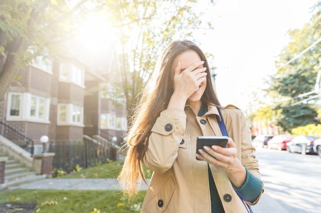 Femme avec smartphone en riant et couvrant le visage avec la main