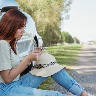 Femme avec smartphone s'appuyant contre sa voiture