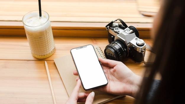 Femme avec smartphone et tasse de café