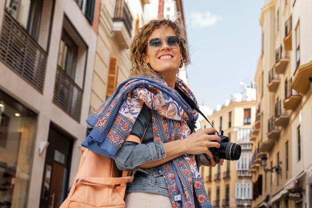 Femme smiley coup moyen avec appareil photo