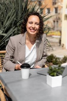 Femme smiley coup moyen avec café