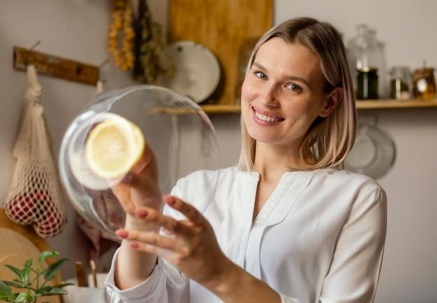 Femme smiley coup moyen nettoyage avec du citron