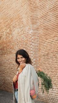 Femme smiley à l'extérieur avec des sacs d'épicerie et de l'espace de copie