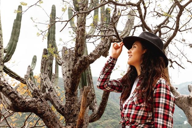 Femme smiley faible angle avec un chapeau dans la nature