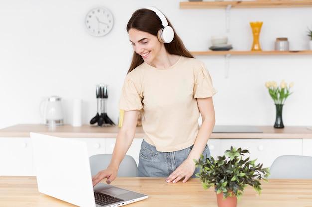 Femme smiley mettant de la musique sur son casque à partir d'un ordinateur portable