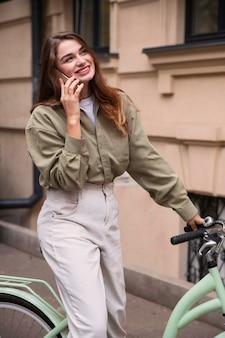 Femme smiley parlant sur son smartphone en faisant du vélo