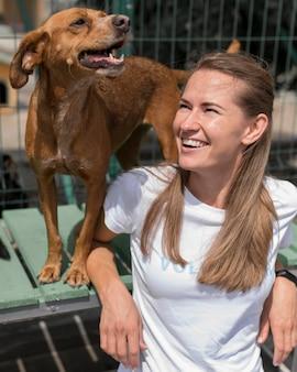 Femme smiley passer du temps avec un chien de sauvetage mignon au refuge