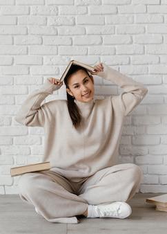 Femme smiley plein coup avec livre sur la tête