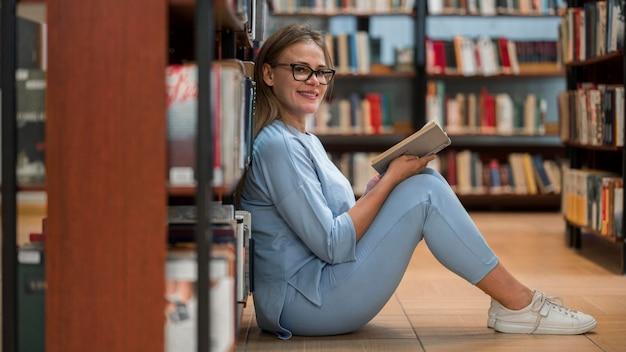 Femme smiley plein coup avec livre