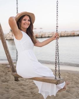 Femme smiley plein coup se balançant à la plage