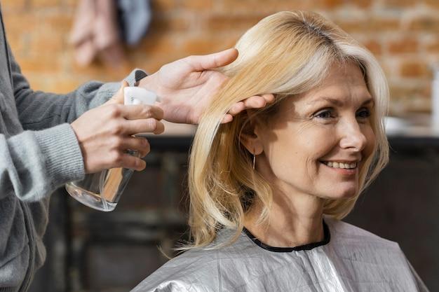 Femme smiley se prépare pour une coupe de cheveux à la maison