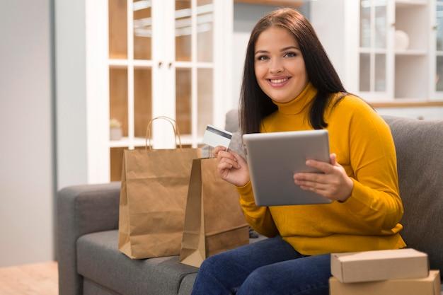 Femme smiley vérifiant la tablette pour un nouvel achat
