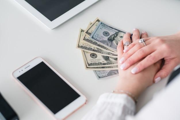 Femme smm réussie. faire de l'argent. femme au lieu de travail avec des billets d'un dollar en mains.