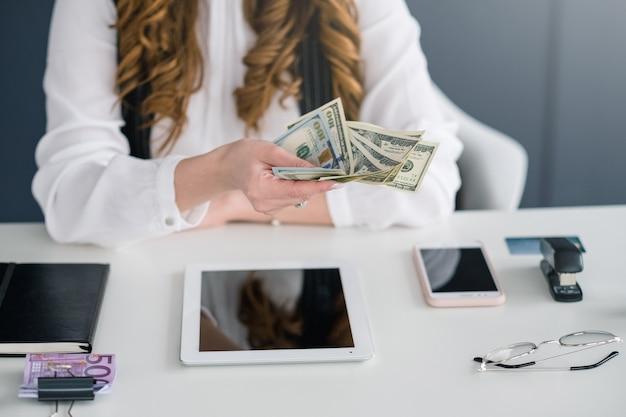 Femme smm réussie. femme au travail avec des billets d'un dollar en mains. bon travail, bon profit.