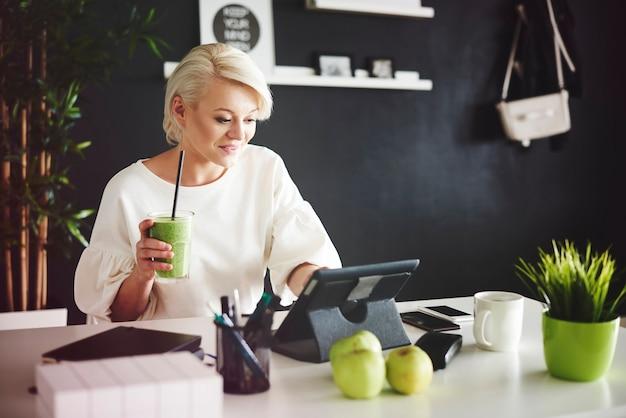 Femme avec smoothie à l'aide d'une tablette numérique à son bureau