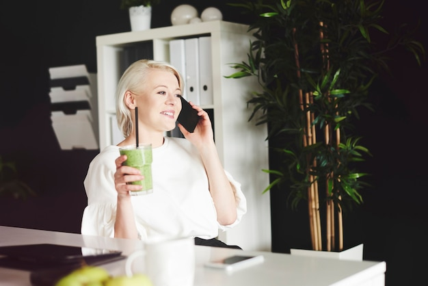Femme avec smoothie a une conversation par téléphone