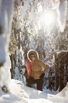 Femme avec snowboard marchant sur la montagne enneigée
