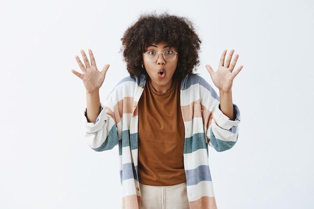 Femme sociable et créative excitée avec une coiffure afro levant les paumes et les lèvres pliantes racontant une histoire effrayante lors d'un voyage avec des amis assis près du feu, persuasive et émotive