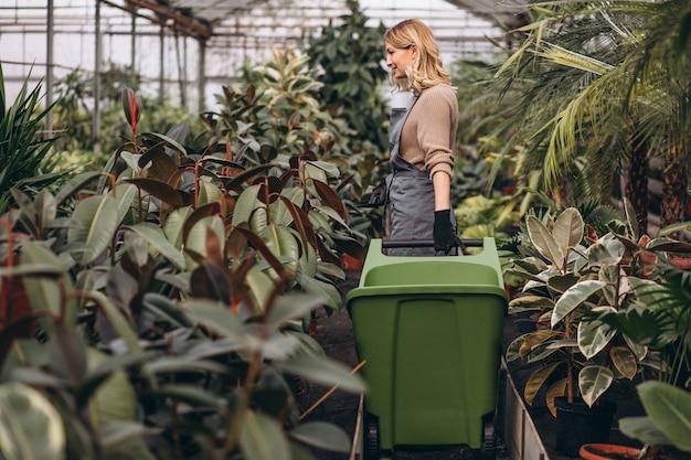Femme soignant des plantes dans une serre