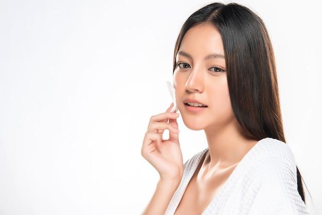 Femme de soin de la peau se démaquillant le visage avec un tampon de coton.,