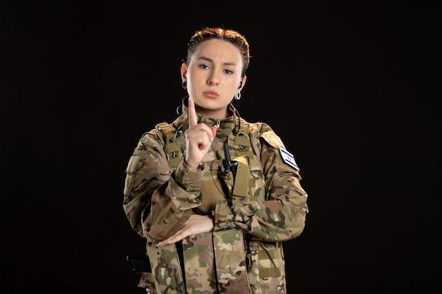 Une femme soldat en camouflage met en garde sur un mur noir
