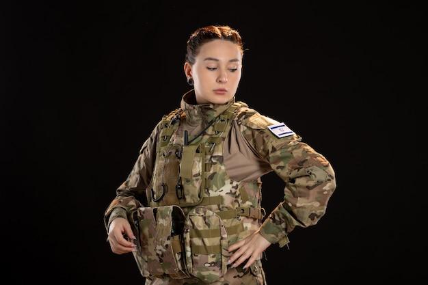 Femme soldat en camouflage sur le mur noir