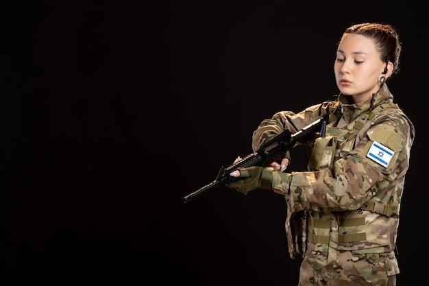 Femme soldat en camouflage visant la mitrailleuse sur mur sombre