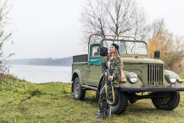 Femme soldat avec fusil posant près de voiture militaire