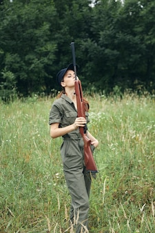 Femme soldat tenant une arme à feu en face de lui combinaison verte voyage lifestyle air frais fond de forêt