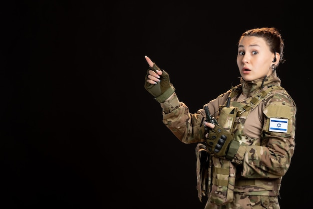 Femme soldat en tenue de camouflage avec grenade sur le mur noir
