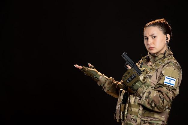 Femme soldat en tenue de camouflage pistolet sur mur noir