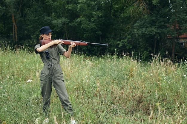 Femme soldat tient une arme à feu dans les mains d'un capuchon noir vue de côté cible close-up