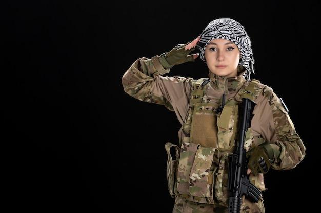Femme soldat en uniforme militaire saluant sur mur noir