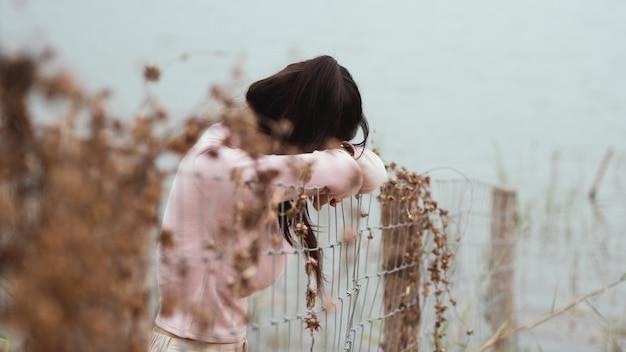 Femme solitaire debout devant la clôture, seule au bord de la rivière. solitude, concept de tristesse.