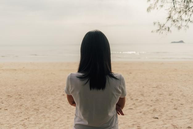 Femme solitaire debout sur la plage et regarde dans la mer.