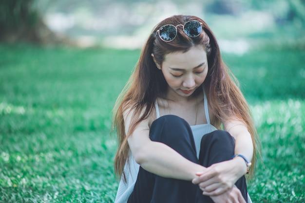 Femme solitude assis dans la pelouse
