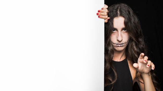 Femme sombre tenant un tableau blanc et la main levée