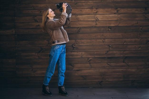 Femme avec son bouledogue français sur fond en bois