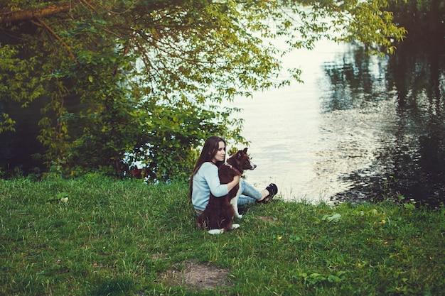 Femme et son chien assis en plein air