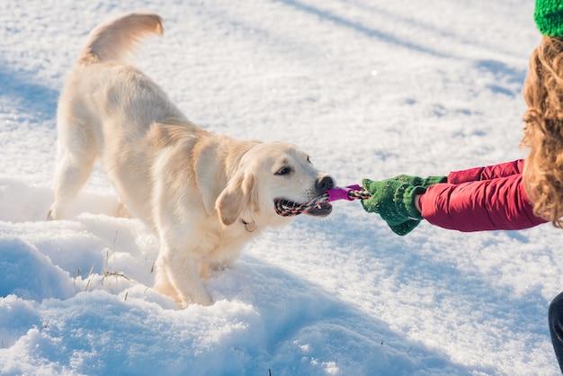Femme et son chien golden retriever jouant dans la neige