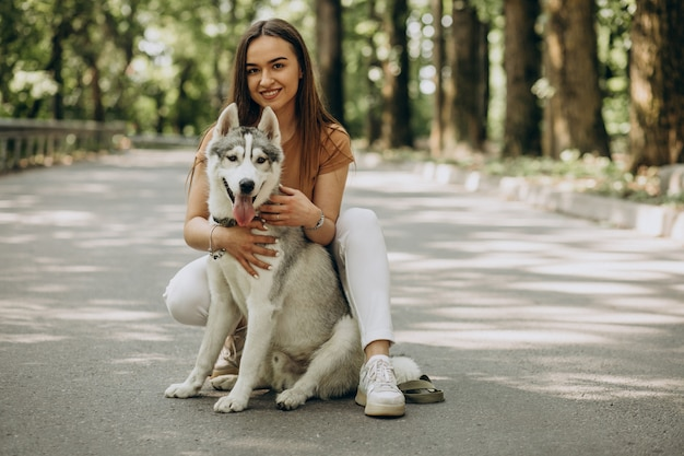 Femme avec son chien husky dans le parc