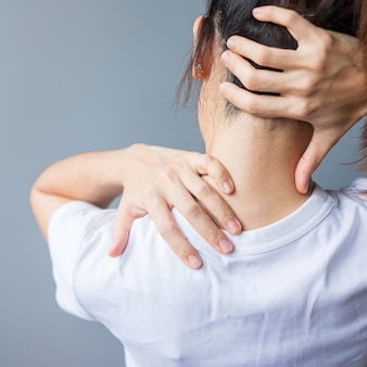 Femme avec son entorse au cou, muscle douloureux pendant le surmenage. fille ayant un problème de corps après le réveil. cou raide, syndrome de bureau et concept ergonomique