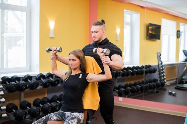 Femme avec son entraîneur personnel de fitness dans la salle de gym exerçant une gymnastique de puissance avec une barre