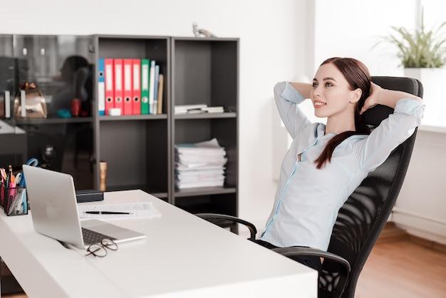 Femme sur son lieu de travail travaillant avec un ordinateur portable au bureau